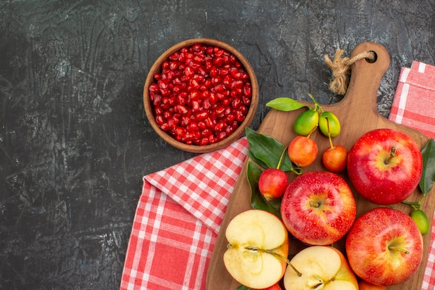 Top view pomegranate bowl of pomegranate apples cherries on the board on the tablecloth