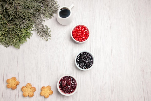 Top view pomegranate bowls of pomegranate jam cookies next to the branches of christmas tree on the table