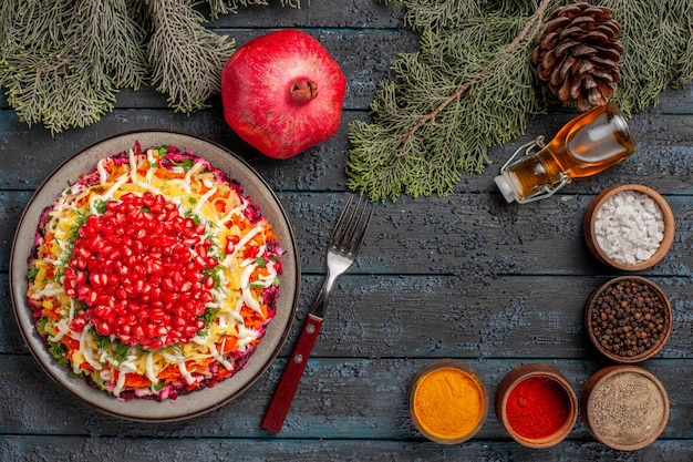 Top view pomegranate dish of potatoes seeds of pomegranate in the plate next to the fork bottle of oil pomegranate spruce branches with cones and colorful spices