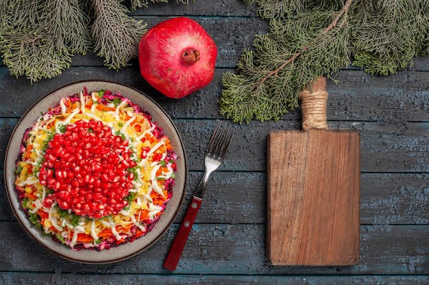 Top view pomegranate dish of potatoes seeds of pomegranate in plate next to the wooden cutting board pomegranate and spruce branches