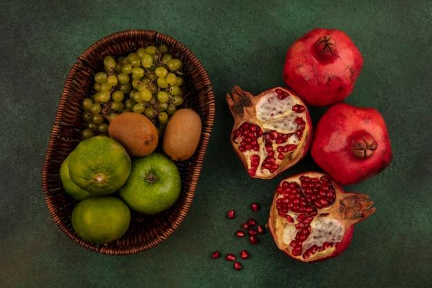Половинки граната с мандаринами, яблоками и киви в корзине, вид сверху