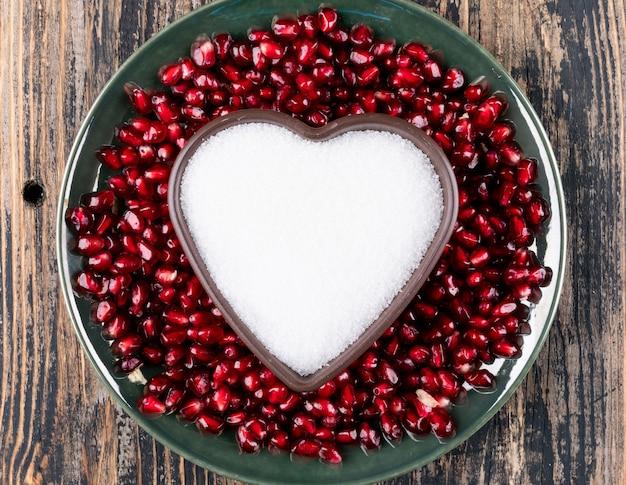 Вид сверху граната в тарелке с сердцем в форме плиты с сахаром на деревянный стол