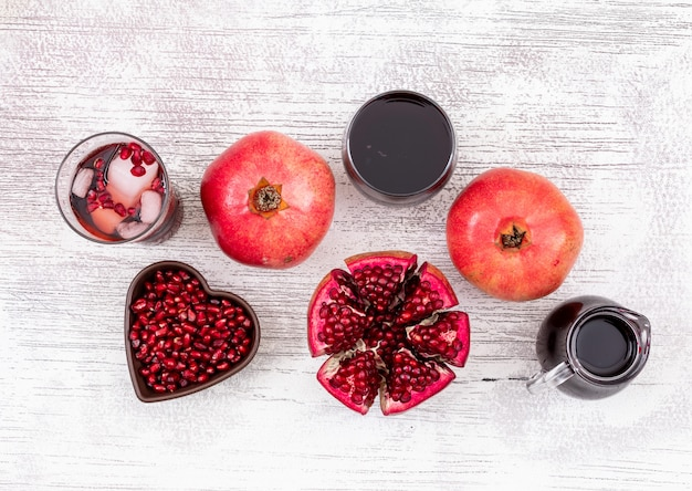 Top view pomegranate juice and pomegranate seeds in heart shaped plate on white wooden table