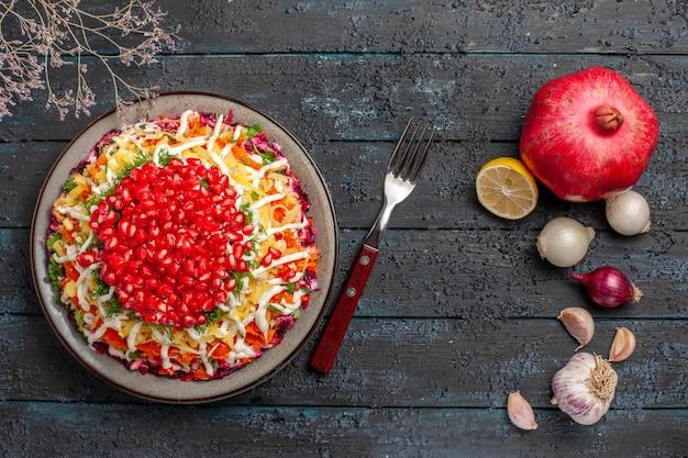 Vista dall'alto melograno limone aglio melograno sbucciato forchetta aglio cipolla limone e piatto di piatto sul tavolo