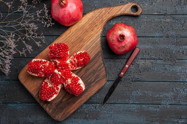 어두운 탁자에 있는 두 석류 사이에 있는 나뭇가지 칼 옆에 있는 커팅 보드에 있는 석류 알약