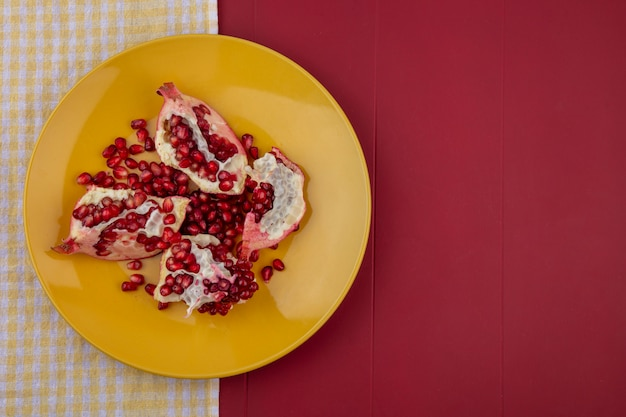 Vista dall'alto di pezzi di melograno e bacche nel piatto sul panno plaid e bordo superficie