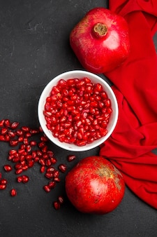 Top view pomegranate pomegranate seeds in the bowl two pomegranates red tablecloth