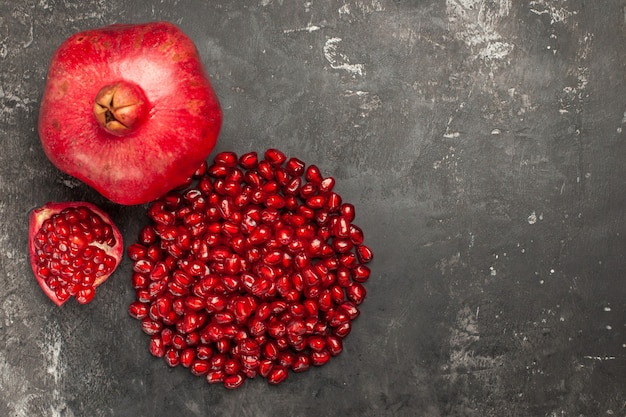 Top view of pomegranate pomegranate seeds on dark surface