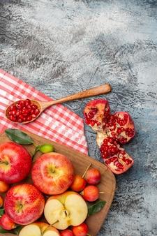 Vista dall'alto melograno melograno cucchiaio mele ciliegie sul bordo sulla tovaglia