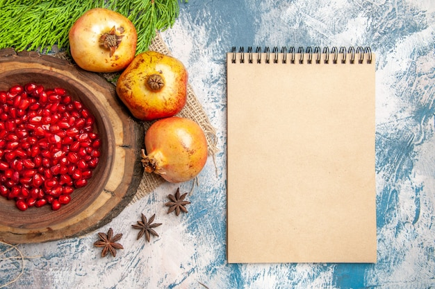 Vista dall'alto semi di melograno in ciotola su tavola di legno dell'albero semi di anice cannella melograni un blocco note su sfondo blu-bianco