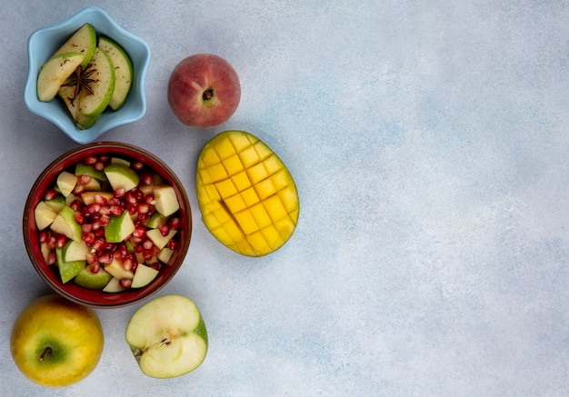 Top view of pomegranate seeds and chopped apples in a red bowl with sliced mango and fresh fruits on white surface