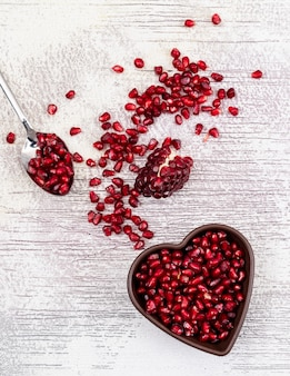 Top view pomegranate seeds in heart shaped plate on white wooden table