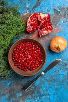 Вид сверху семена граната в миске обеденный нож срезанная ветка сосны граната на синей поверхности