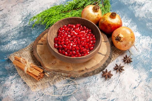 나무 판자에 있는 그릇에 있는 상위 뷰 석류 씨앗 파란색 흰색 배경에 계피 아니스 씨앗 석류