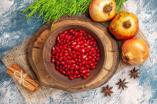 나무 판자에 있는 그릇에 있는 상위 뷰 석류 씨앗 계피 아니스 씨앗 파란색 흰색 배경에 석류 나무 가지