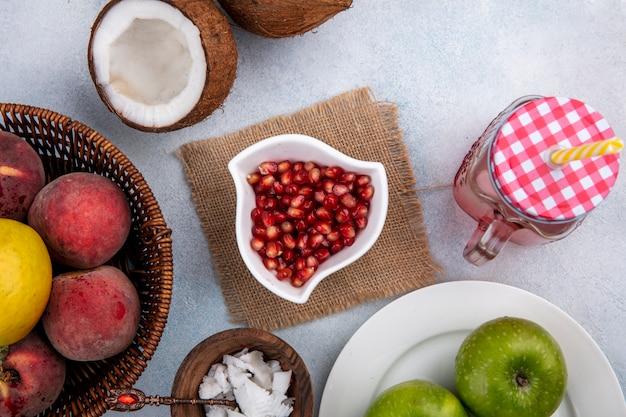 Vista dall'alto di semi di melograno in una ciotola bianca sul panno di sacco con polpe di cocco in una ciotola di legno e mela verde in un piatto bianco sulla superficie bianca