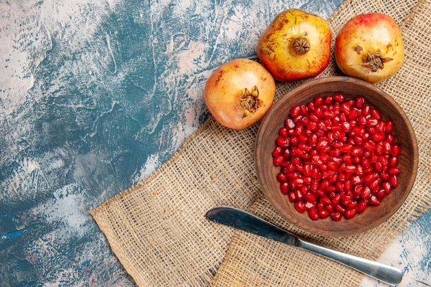 Top view pomegranate seeds in wooden bowl dinner knife pomegranates on blue-white background free space