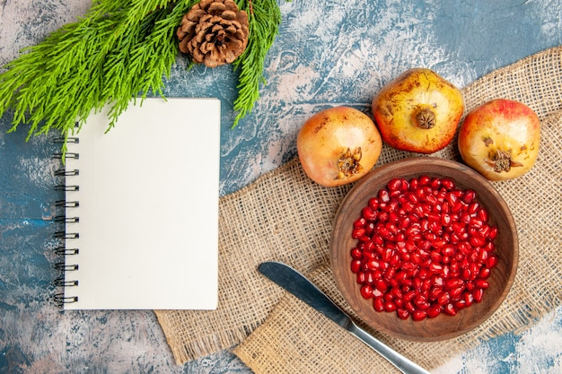 Top view pomegranate seeds in wooden bowl dinner knife pomegranates notebook pine tree branch on blue-white background