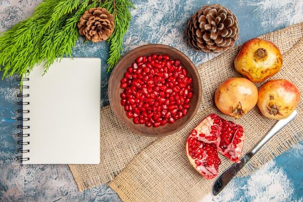 Vista dall'alto semi di melograno in ciotola di legno coltello da pranzo melograni notebook ramo di pino e coni su superficie blu-bianca