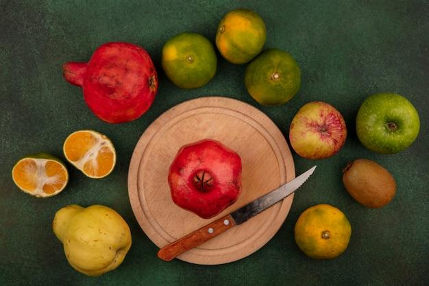 Вид сверху гранат с ножом на подставке с грушами, мандаринами и яблоком