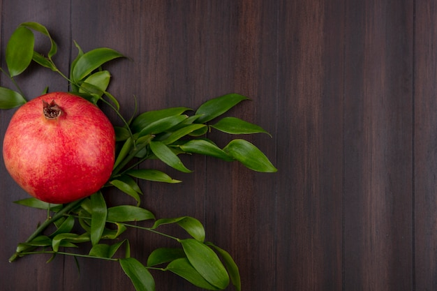 Top view of pomegranate with leaf branch on wooden surface
