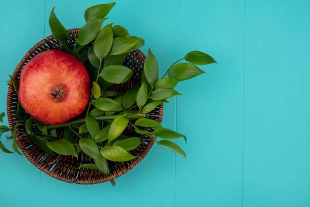 Top view of pomegranate with leaf branches in a basket on a blue surface