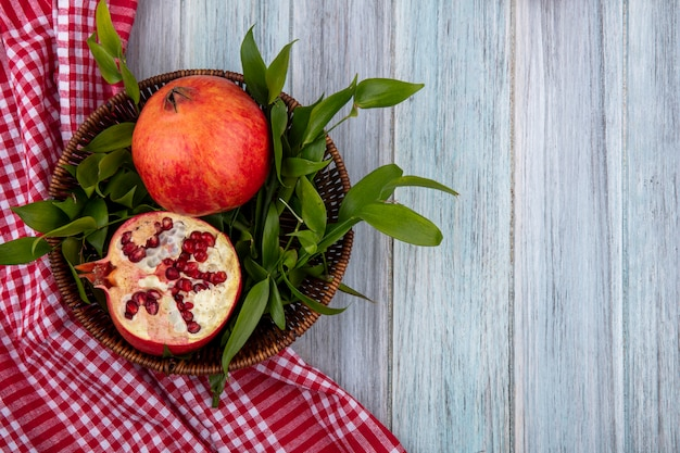 Top view of pomegranate with leaf branches in a basket with a red checkered towel on a gray surface