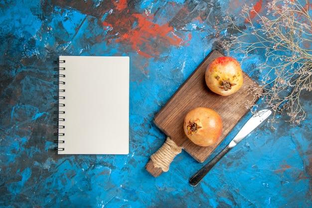 Vista dall'alto melograni sul tagliere coltello da pranzo un taccuino su sfondo astratto blu