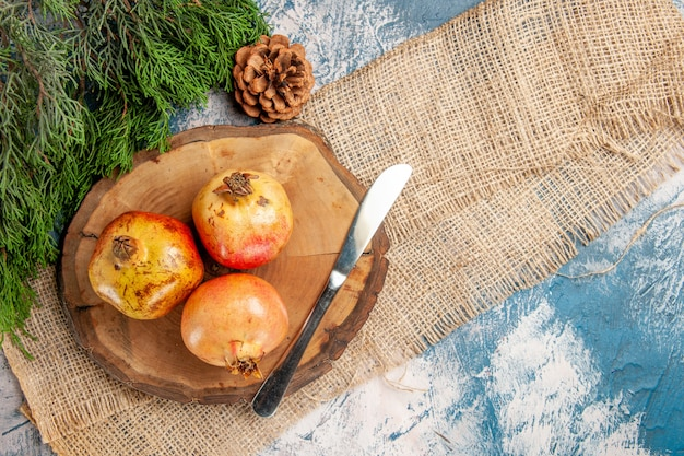 Top view pomegranates dinner knife on round tree wood cutting board pine tree branch on blue-white surface