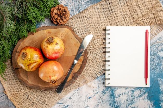 Vista dall'alto coltello da pranzo di melograni su tagliere di legno di albero rotondo taccuino di rami di pino con penna rossa su superficie blu-bianca