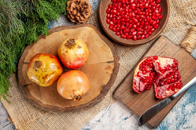 Top view pomegranates on round cutting board pomegranate seeds in bowl a cut pomegranate on chopping board pine tree branch on blue-white background