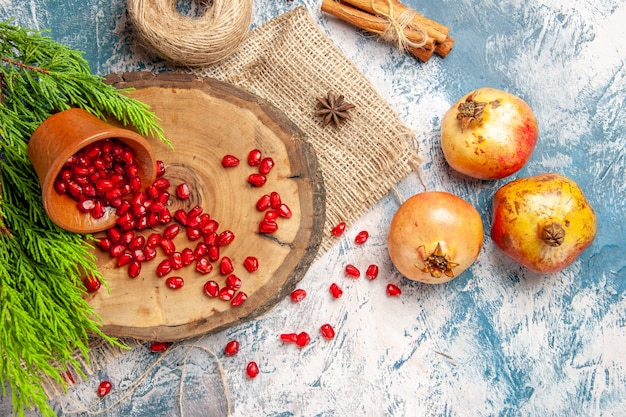 Top view pomegranates scattered pomegranate seeds in bowl on tree wood board straw thread cinnamon anise seeds tree branch on blue-white background