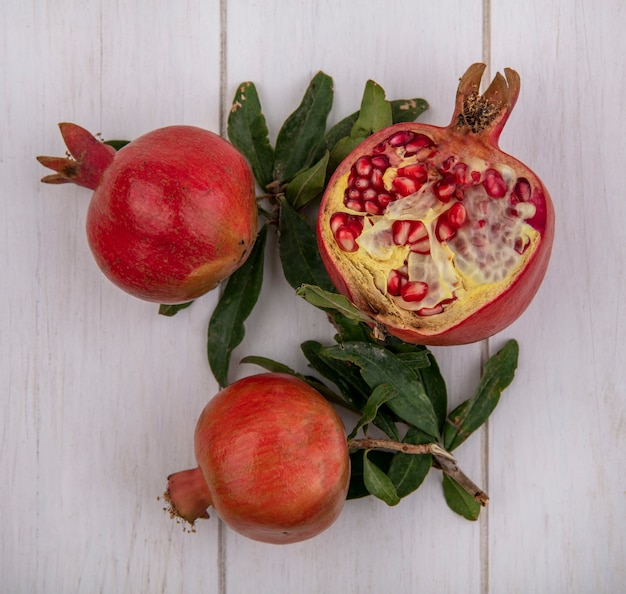 Top view pomegranates with branches of leaves on a white background