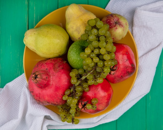 Top view pomegranates with pears apples and grapes on a plate