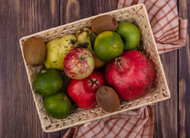 Вид сверху гранаты с мандаринами, яблоками, грушами и киви в корзине на деревянном столе