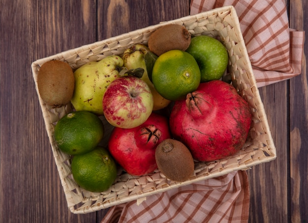 Top view pomegranates with tangerines apples pears and kiwi in a basket on wooden table