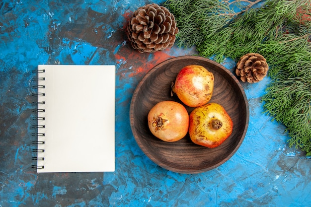 Top view pomegranates on wooden plate pine tree branch and cones a notebook on blue background
