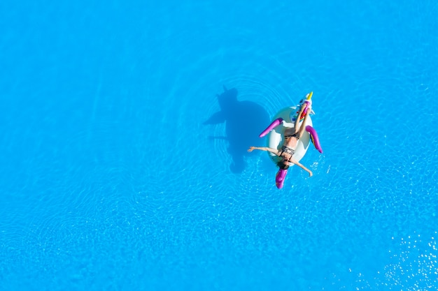 Top view of the pool with a girl in a swimsuit on an inflatable circle. relaxing and tanning in the summer.