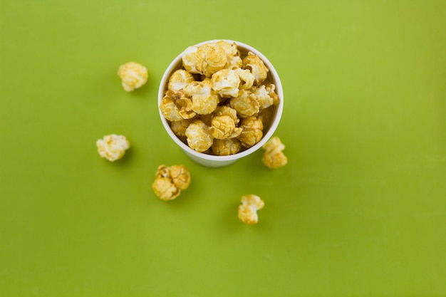 Top view pop corn in a paper cup olive green bacground
