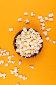 Top view of popcorn in bowl on yellow  vertical