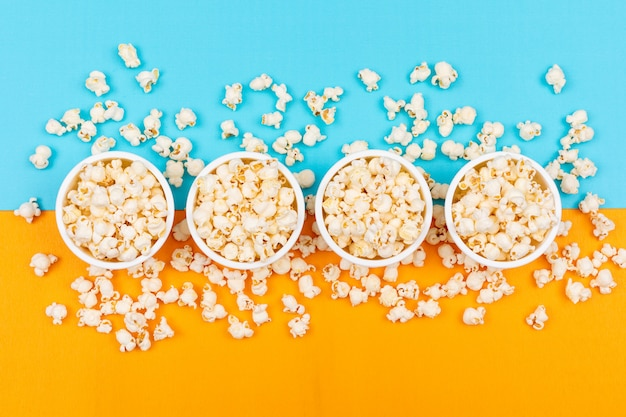 Top view of popcorn in bowls on blue and yellow  horizontal