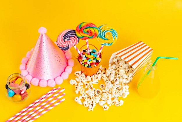 A top view popcorn and candies along with pink funny cap and cocktail