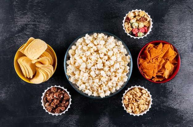 Top view of popcorn and chips in bowls on black  horizontal