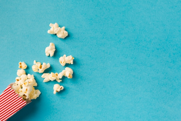 Top view popcorn composition on blue background with copy space