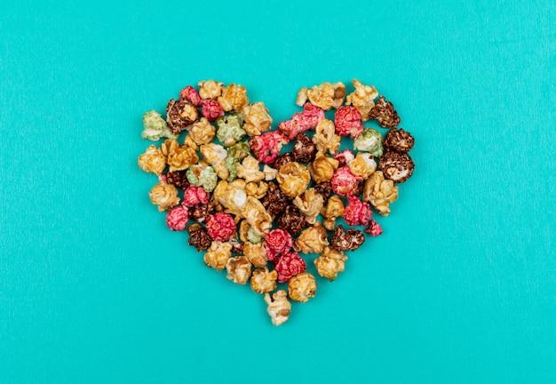 Vista superiore del cuore di popcorn su orizzontale blu
