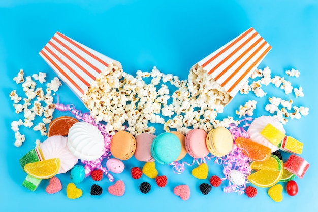 A top view popcorn and macarons colorful marmalades candies and other sweeties