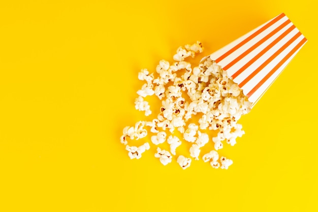 A top view popcorn package salted tasty spread all over the yellow background