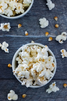 Top view of popcorn in a white bowl with a blue with popcorn.