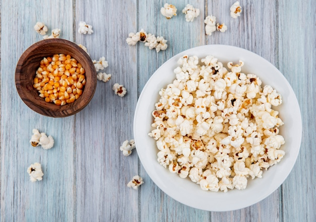 Top view of popcorn on a white plate with corns on a wooden bowl on grey surface