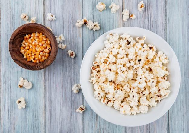 Vista dall'alto di popcorn su un piatto bianco con semi su una ciotola di legno sulla superficie grigia